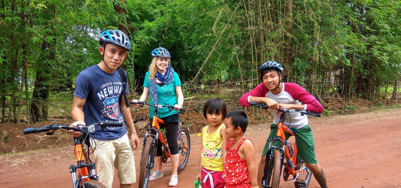 https://takemetomyanmar.com/wp-content/uploads/2019/07/Mountain-bikers-with-children-in-Hpa-an-1280x600.jpg